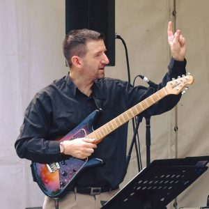 Saul Richardson, one of the JWA teachers, on stage holding an electric guitar and pointing skywards