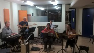 A group of adult students playing in a jazz band at JWA near North Sydney with guitar, bass, drums, piano, and sax