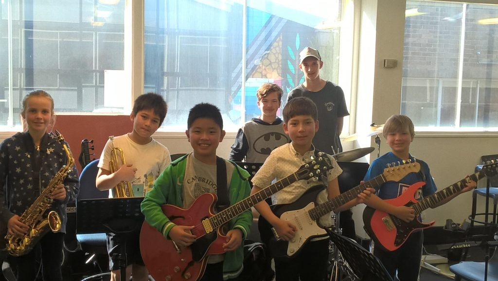 A children's jazz band with three guitarists, trumpet, saxophone, piano, bass and drums