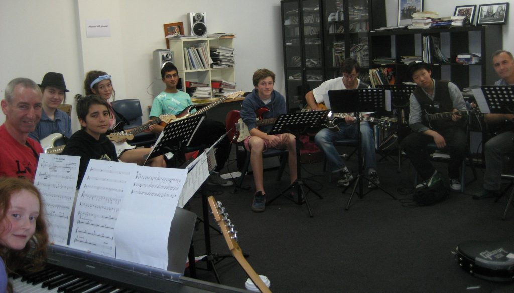 A group guitar lesson, ten students boys and girls, children, teens and adults seated in a semicircle.