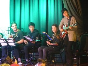 Group of 4 guitar students from JWA studio in Crows nest on stage at a concert