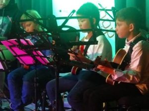 The young guitar students from JWA studio near North Sydney on stage performing
